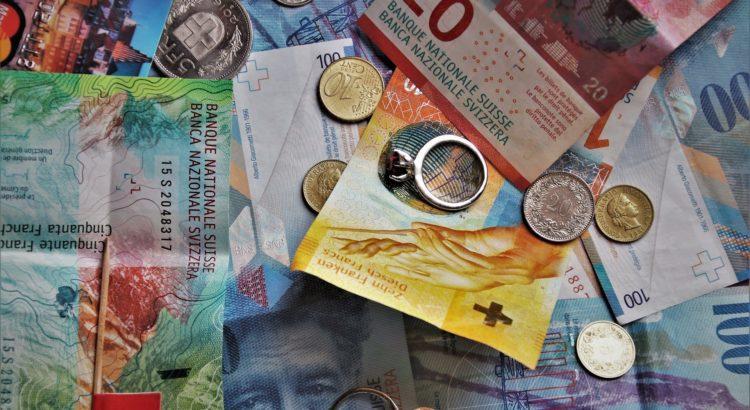 Billets de 50, 20 et 10 francs suisses éparses sur une table avec quelques pièces de monnaie.