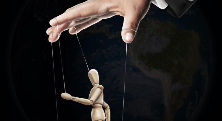 Une main de marionnettiste, doigts écartés, paume vers le bas, manipule un pantin en bois nu, dont le corps présenté sur son profil gauche est en pose de mouvement, jambe droite genou à l'équert, levé à 90 degrés, bras droit lancé en avant, parallèle au genou levé, à hauteur de poitrine.