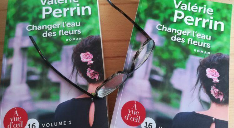 """Posés sur une table en bois de chêne, les deux volumes du roman """"Changer l'eau des fleurs"""" de Valérie Perrin, sur lesquelles est posée, de travers, une paire de lunettes de vue, branches déployées vers la gauche de la photo. On devine que ce sont des doubles-foyers."""